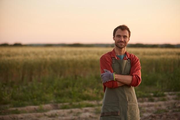 日没時にフィールドに立って、カメラ、コピースペースに笑みを浮かべて腕を組んで自信を持ってポーズをとる若い農夫の肖像画を腰に当てる
