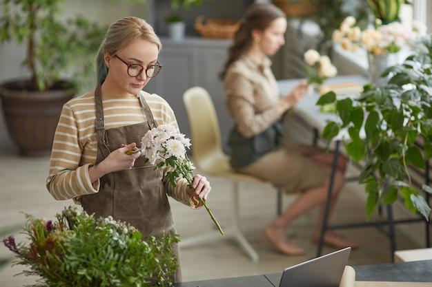 中小企業のワークショップ、コピースペースで花束を作成しながら花の組成物を配置する若い女性の花屋の肖像画をウエストアップ