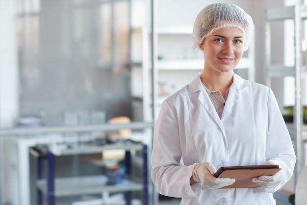 디지털 태블릿을 들고 의료 실험실에 서있는 동안 카메라에 웃고 젊은 여성 과학자의 초상화를 허리, 복사 공간