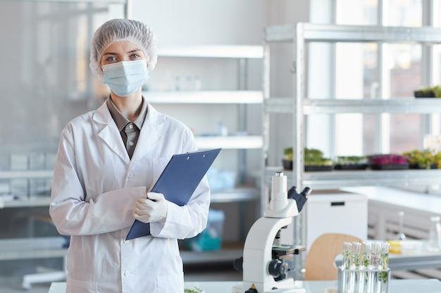 얼굴 마스크를 착용하고 중간 실험실에 서서 클립 보드를 들고있는 동안 카메라를보고 젊은 여성 과학자의 초상화를 허리, 복사 공간