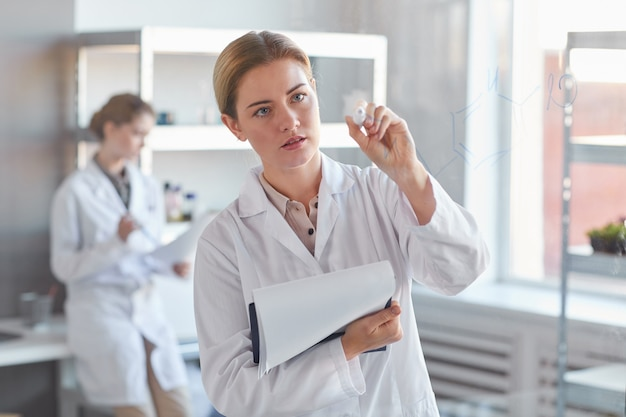 유리 벽에 쓰기 및 의료 실험실에 서있는 동안 클립 보드를 들고 젊은 여성 과학자의 초상화를 허리, 복사 공간