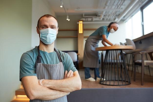 マスクとエプロンを身に着けている若い男性ウェイターの肖像画を腰に当てて、カフェに立っている間、女性がバックグラウンドで掃除をしている間、安全対策、コピースペース