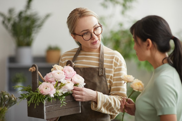 フラワーショップで働いている間、顧客に花束を与える若い女性の肖像画をウエストアップ