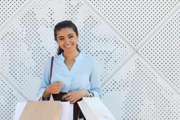 쇼핑몰에서 야외 질감 흰색 표면에 서있는 동안 쇼핑 가방을 들고 카메라에 웃 고 젊은 여자의 초상화를 허리, 복사 공간