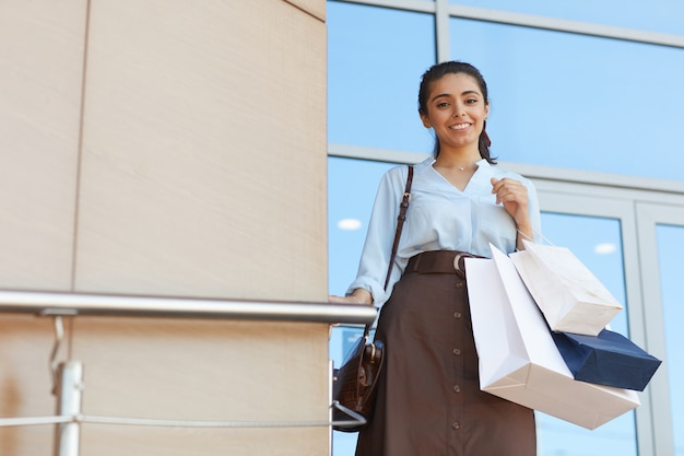 쇼핑 가방을 들고 쇼핑몰 입구에 야외에서 서있는 동안 카메라에 웃고 젊은 여자의 초상화를 허리, 복사 공간