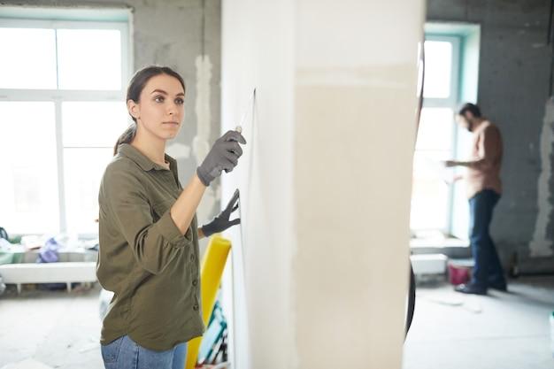 집을 개조하는 동안 벽을 부드럽게하는 젊은 여자의 초상화를 허리, 복사 공간