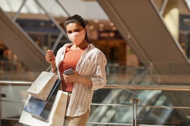 쇼핑몰에서 쇼핑하는 동안 마스크를 착용하는 젊은 여성의 초상화를 허리와 복사 공간