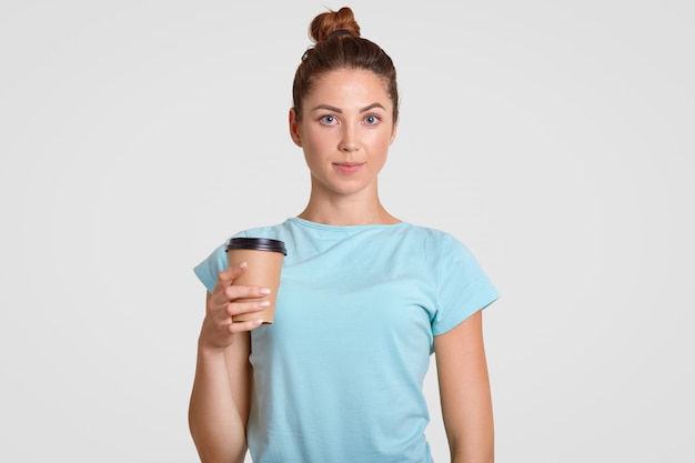 Waist up portrait of pleasant looking woman with hair bun, dressed in casual light blue t shirt