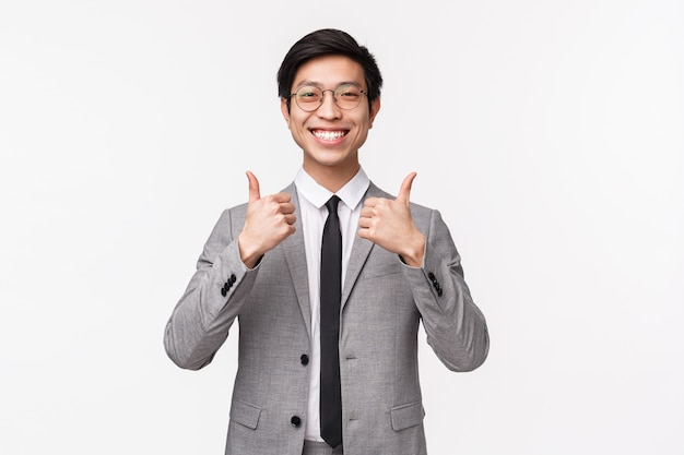 Waist-up portrait of pleased, fully satisfied asian young man in grey suit, showing thumbs-up and smiling with approval, like awesome concept. recommend service, assure it is best deal