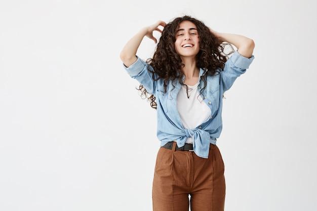 Il ritratto in vita di un modello femminile di brunnete emotivo positivo indossa larghi sorrisi di camicia di jeans, gioca con lunghi capelli ondulati, gioisce la vita, dimostra denti bianchi. bellezza, felicità e giovinezza