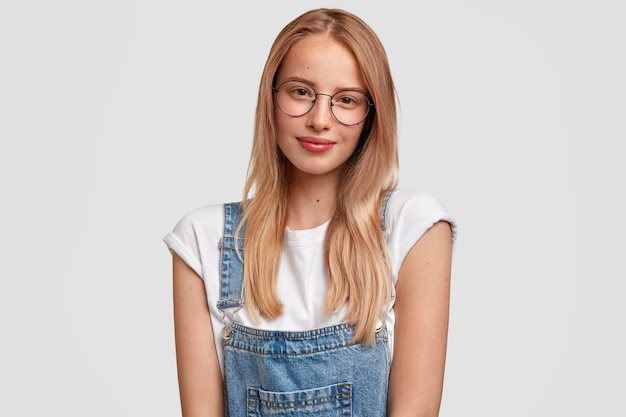 Waist up portrait of pretty young european female with long hair, wears glasses and overalls, feels satisfied to hear results of exam, looks with friendly expression, isolated over white wall