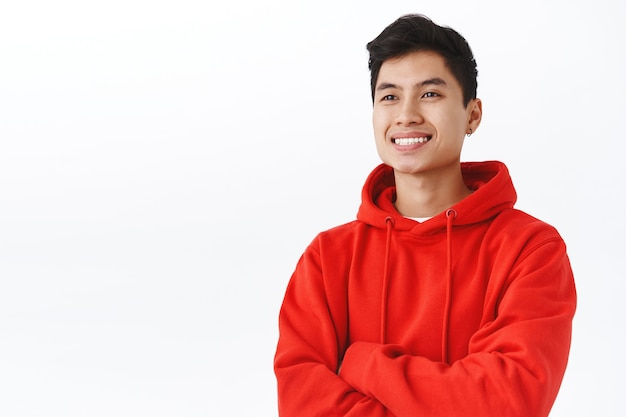 Waist-up portrait of professional, successful young asian man seeing good profit, made investment or finished deal, looking pleased, gaze away satisfied with beaming smile, white wall.