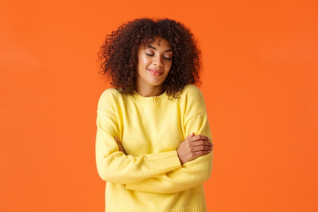 Waist-up portrait romantic lovely young woman dreaming about travelling somewhere warm on winter holidays, close eyes and smiling sensually, embracing own body, standing orange