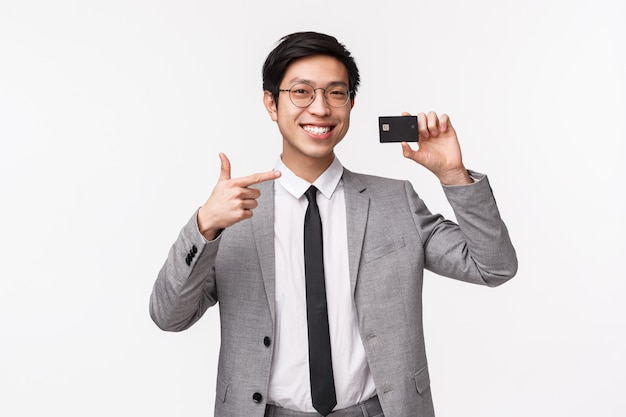 Waist-up portrait of satisfied, good-looking young assured asian man in suit, showing credit card, pointing at it with pleased smile, recommend using non-cash payments, on a white wall