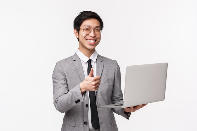 Waist-up portrait of satisfied, happy and pleased young asian male entrepreneur, it programmer in suit, introduce his new project, show thumbs-up in approval and holding laptop, on a white wall