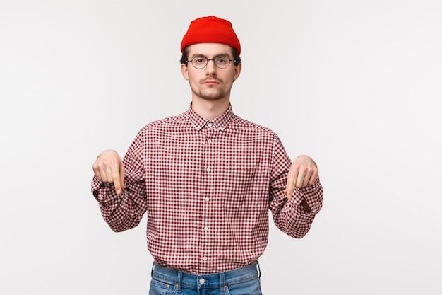 チェックシャツ、赤いビーニー、眼鏡で厳格なカメラを探している上半身の深刻な格好の若い上半身肖像画