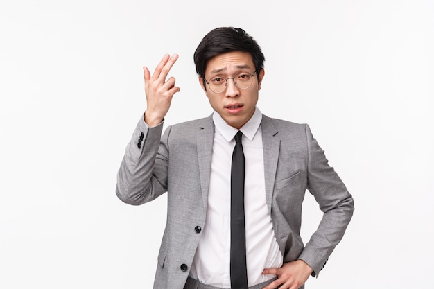 Waist-up portrait of serious-looking disappointed young asian businessman complaining, disapprove bad project, unproductive work, scolding employee not thinking before acting