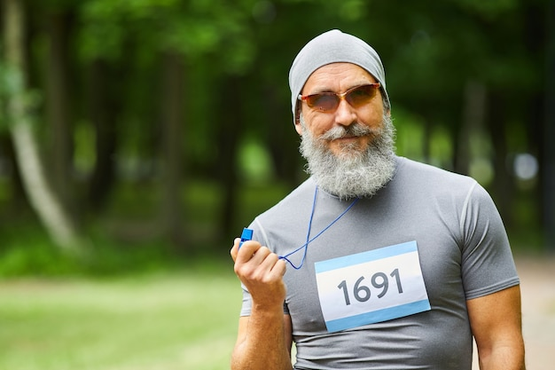 Waist up portrait shot of modern bearded mature adult man wearing sports outfit holding whistle looking at camera