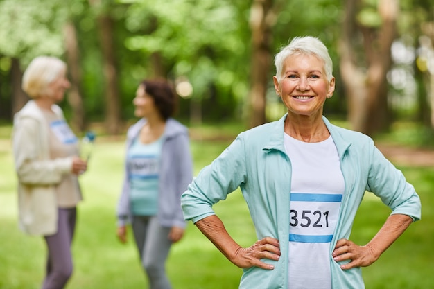 カメラに向かって笑顔の後ろでチャットしている彼女の友人と公園に立っているスポーツ服を着て短いヘアカットで楽しいシニアのポートレートショットを腰に