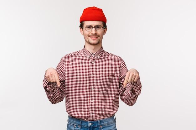 Портрет талии скептически и сомнительно не поддавшийся эмоциям молодой человек в шапке и очках, недовольный гримасой выражает неприязнь и разочарование в последнем обновлении, указывая пальцами вниз