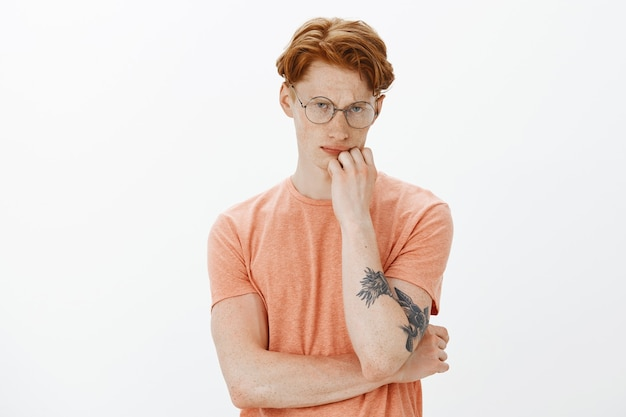 Waist-up portrait of smart and handsome redhead man in glasses looking thoughtful, thinking