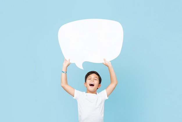 Waist up portrait of smiling asian boy holding up an empty white speech bubble in light blue wall