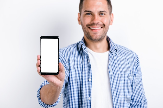 Waist up portrait of smiling bearded man holding smartphone with the screen to the camera and having wide smile. technologies and people concept