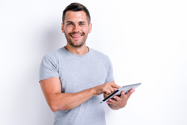 Waist up portrait of smiling bearded man holding a tablet and pointing to the screen with wide smile. technologies and people concept