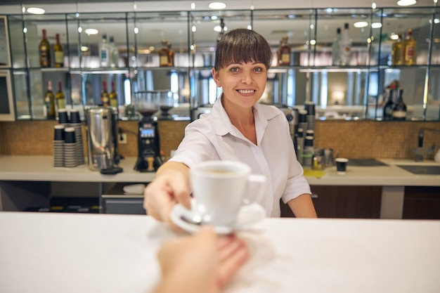 Waist up portrait of smiling beautiful woman working at bar and giving cup of coffee to man