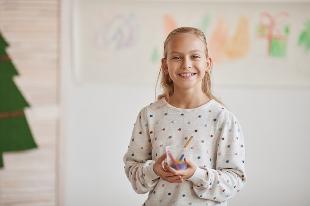 Waist up portrait of smiling blonde girl holding crayons and looking at camera while enjoying art class on christmas, copy space