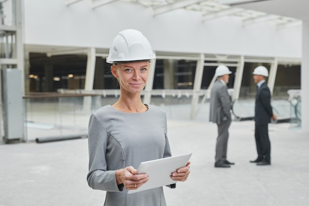 Waist up portrait of smiling businesswoman wearing hardhat and holding tablet while standing at construction site indoors,