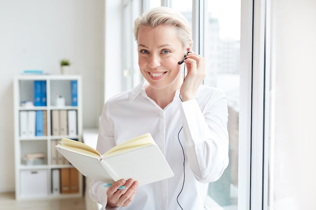 Waist up portrait of smiling businesswoman wearing headset and looking while working in call center