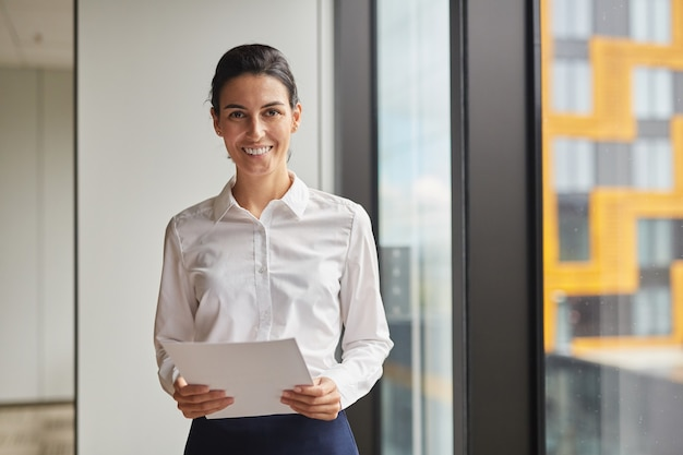 Waist up portrait of smiling businesswoman  while standing by window in office,