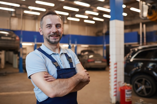 Waist up portrait of smiling car mechanic standing with arms crossed while posing in auto repair shop, copy space