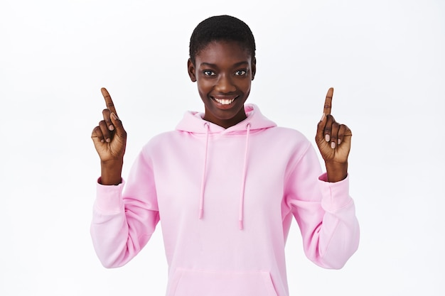 Портрет талии улыбается дружелюбно выглядящая привлекательная афро-американская женщина в розовой толстовке с капюшоном