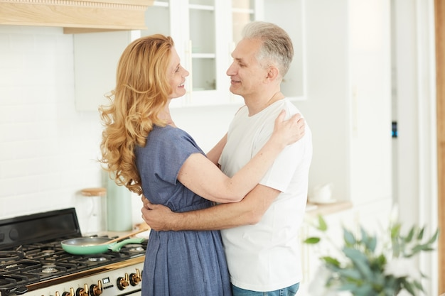 Waist up portrait of smiling mature couple embracing and looking at each other while standing in white kitchen interior at home, copy space