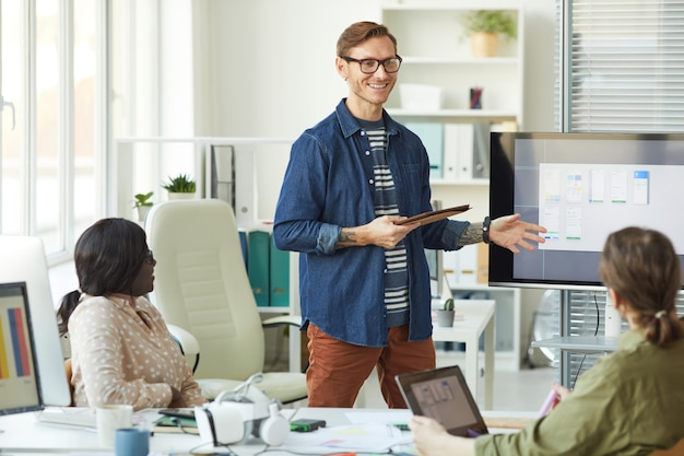 Waist up portrait of smiling tattooed man pointing at digital screen while planning project during meeting with it development team, copy space