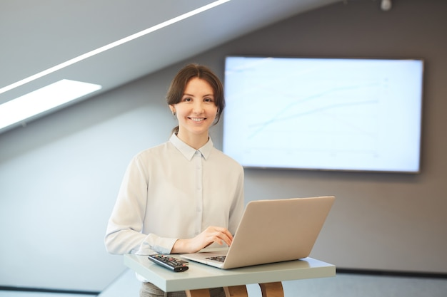 Waist up portrait of smiling young businesswoman looking at camera while posing at standing table with laptop in minimal interior with presentation screen in background, copy space