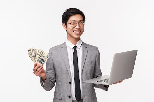 Waist-up portrait of successful rich asian businessman, it programmer selling application