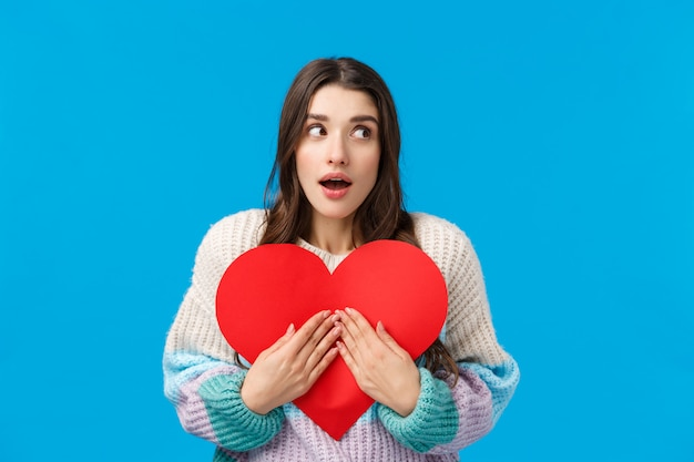 Waist-up portrait surprised and curious wondered caucasian woman dont know who prepared valentines-day gift for her, looking around open mouth amazed, embracing cute red cardboard heart