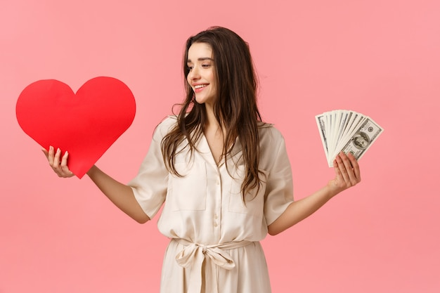 Waist-up portrait surprised and determined brunette woman making her choice towards true love, looking at heart, holding valentines card and cash, dont care wealth and money, pink wall