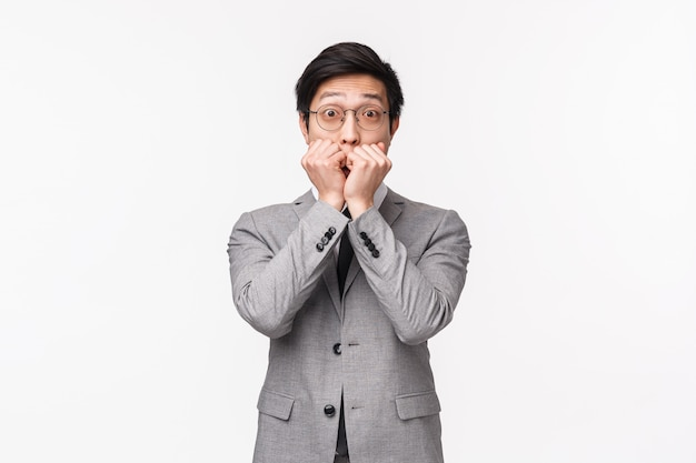 Waist-up portrait of surprised and impressed young handsome asian businessman gossiping with coworker, being amazed gasping, cover mouth and staring thrilled , on a white wall