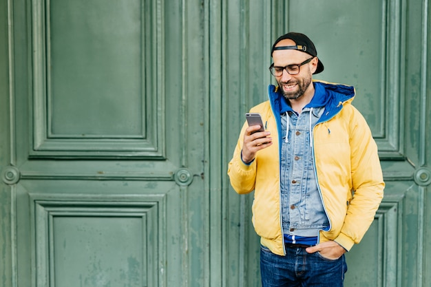 Waist up portrait of trendy hipster with beard dressed in casual clothes holding hand