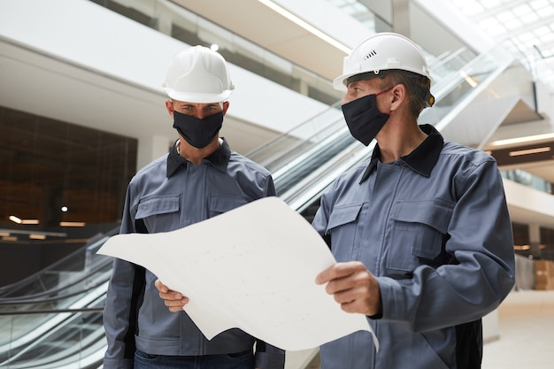 Waist up portrait of two construction workers wearing masks and discussing plans while standing in shopping mall or office building
