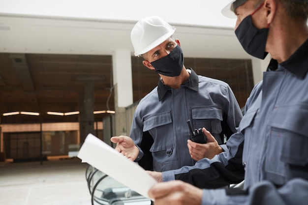 Waist up portrait of two construction workers wearing masks and discussing plans while standing in shopping mall or office building,