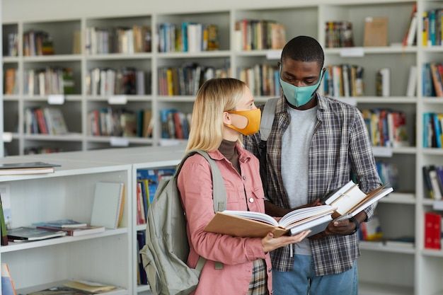 Waist up portrait of two students wearing masks while standing in school library and holding books,