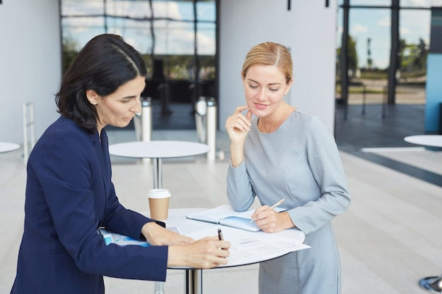 Waist up portrait of two successful businesswomen discussing deal while standing by cafe table in airport or office building