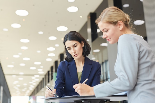 Waist up portrait of two successful businesswomen discussing deal while standing by cafe table in airport or office building,