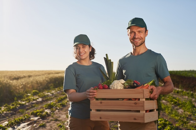 Waist up portrait of two workers holding box of vegetables and smiling at camera while standing ant plantation outdoors, copy space