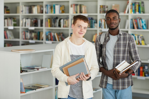 Waist up portrait of two young men in school library holding books and smiling happily at camera,